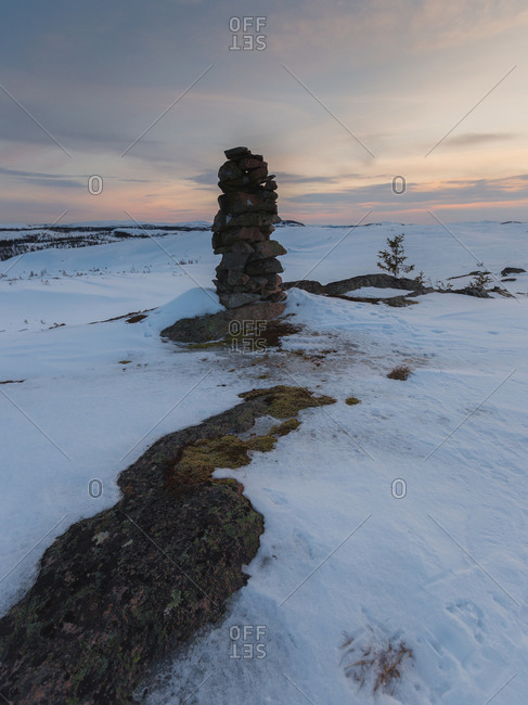Marker stone and snowdrifts along a barren hillside