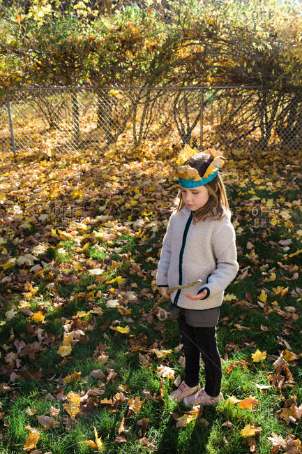 Girl standing outside in a leaf covered yard wearing a paper crown