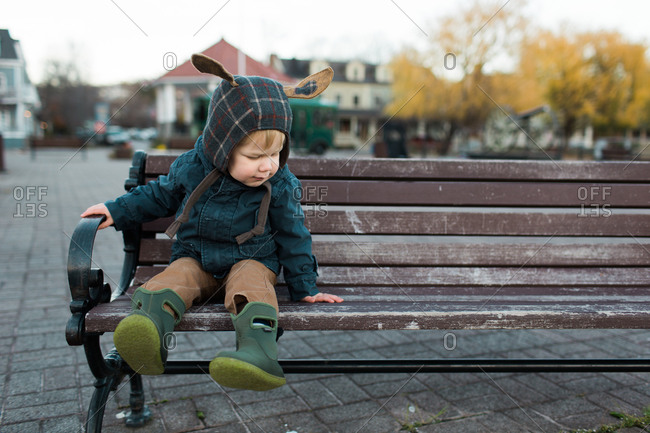 Toddler sitting on a park bench dressed in winter clothes