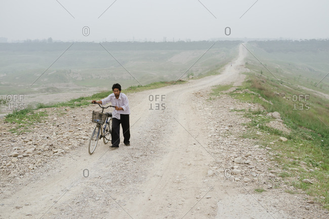 Beijing, China - July 20, 2012: A man wheeling his bicycle up a hill in a suburb of Beijing, China
