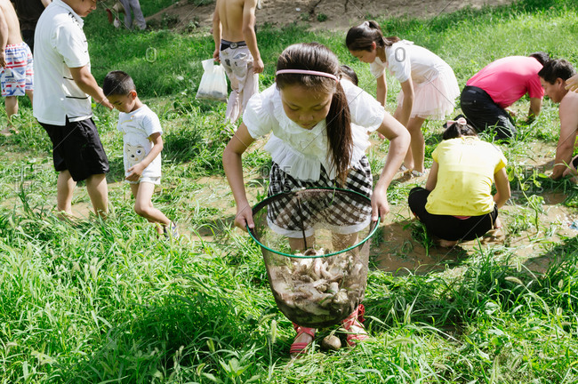 Beijing, China - July 22, 2012: A girl holding a basket of fish while others are looking for fish in mud