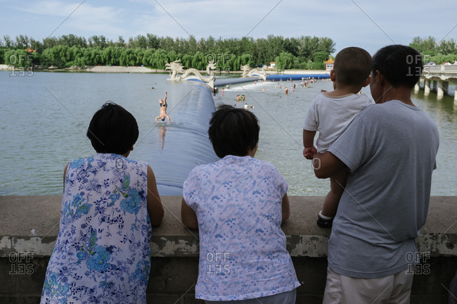 People looking at a river where people are swimming