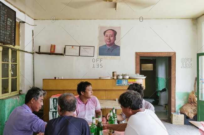 Beijing, China - July 27, 2012: Five men are having lunch together in a small restaurant, Beijing, China