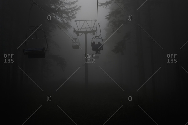Germany, silhouettes of people using chairlift at haze