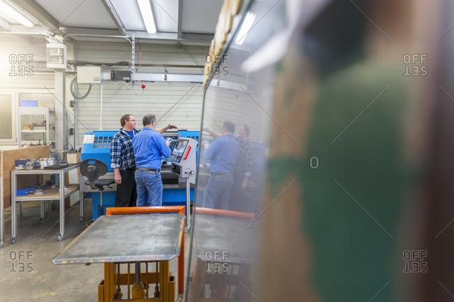 Two men in factory talking at eroding machine