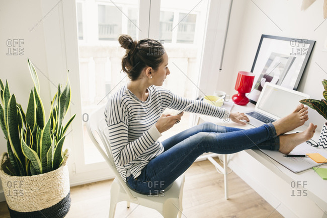 Woman at home laying feet on table using laptop