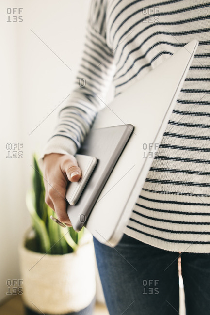 Woman holding portable devices in different sizes