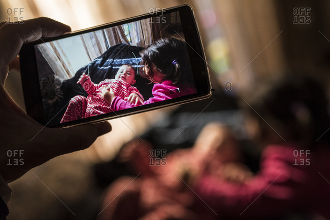 Father taking picture of his children with smartphone, close-up