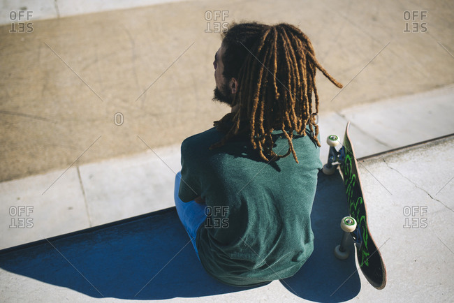 Back view of young man with dreadlocks sitting in a skatepark