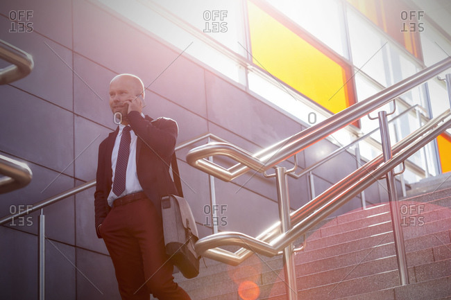 Businessman on stairs talking on cell phone