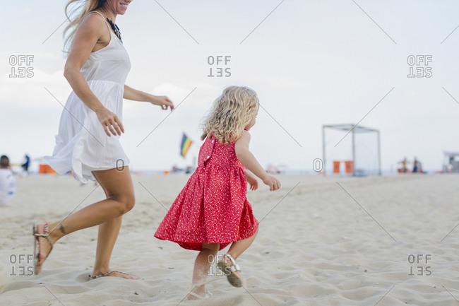 Brasil, Rio de Janeiro, happy mother and daughter running on Copacabana beach