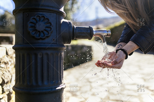 Young woman washing hands at a well