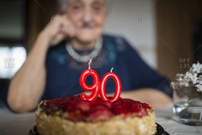 Candles on a birthday cake of a senior woman celebrating her ninetieth birthday