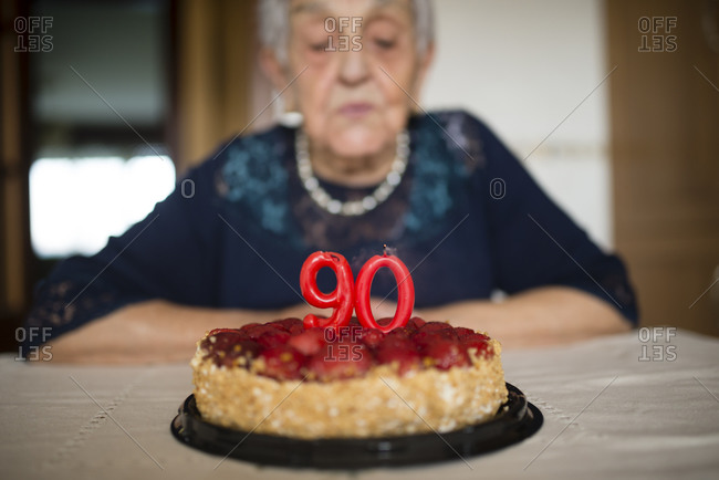 Portrait of senior woman blowing out the candles on her birthday cake
