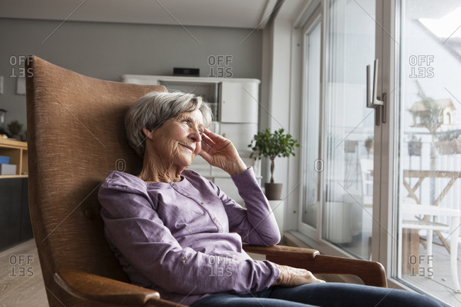 Portrait of senior woman sitting on armchair at home looking through window