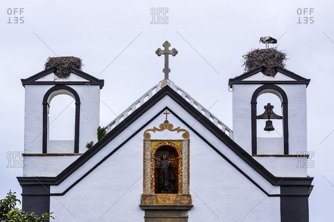 Portugal, Algarve, Faro, Stork perching in stork's nest on church