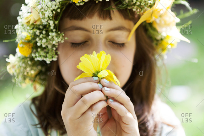 Portrait of little girl with wreath of flowers smelling yellow blossom