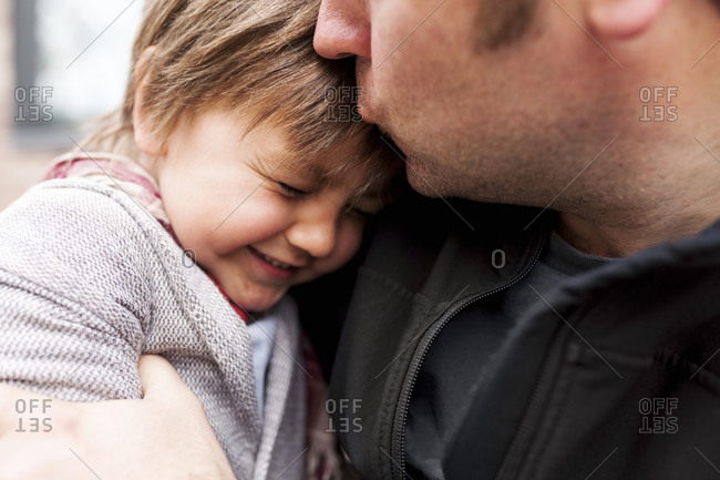 Father kissing his little son, close-up