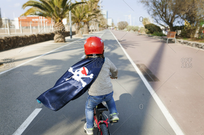 Spain, Barcelona, back view of little boy with a pirate cape riding bicycle on an empty street