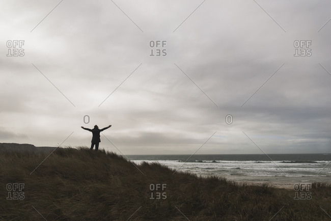 France, Bretagne, Finistere, Crozon peninsula, man standing at the coast under cloudy sky spreading out his arms