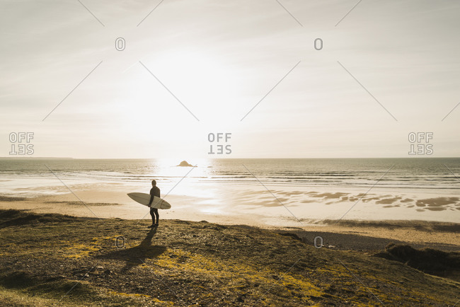France, Bretagne, Finistere, Crozon peninsula, man standing at the coast at sunset with surfboard