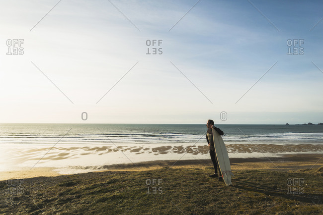 France, Bretagne, Finistere, Crozon peninsula, man standing at the coast with surfboard