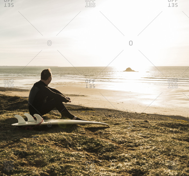 France, Bretagne, Finistere, Crozon peninsula, man sitting at the coast at sunset with surfboard