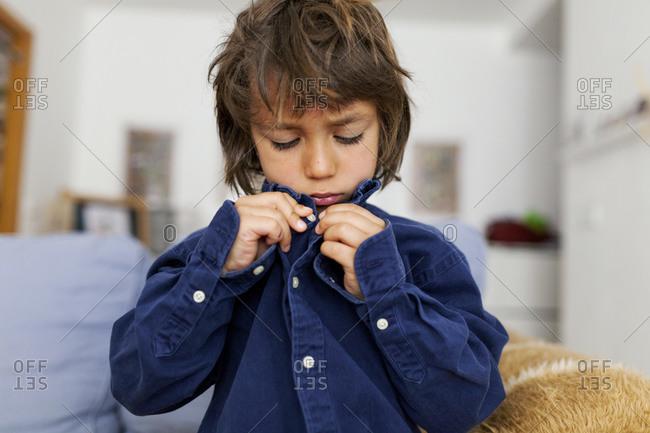 Little boy buttoning his shirt