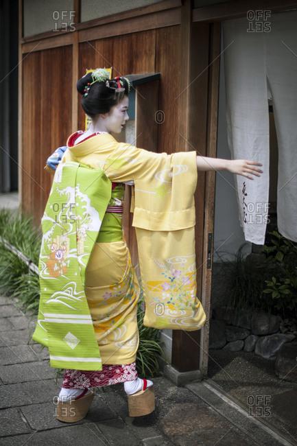 Japan - June 17, 2014: Geisha entering a tea house