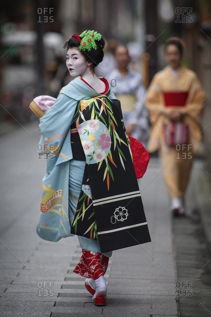 Japan - June 17, 2014: Geisha walking along the street looking over her shoulder