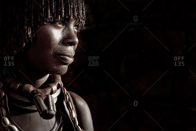 Africa - July 26, 2011: Portrait of an Hamar woman on a dark background