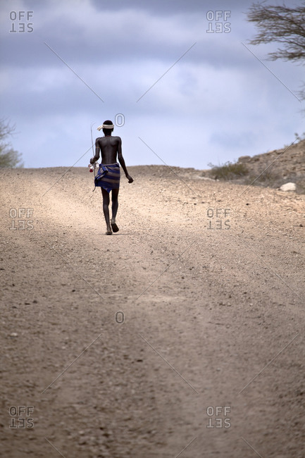 Africa - July 28, 2011: Hamar tribesman walking along a gravel road