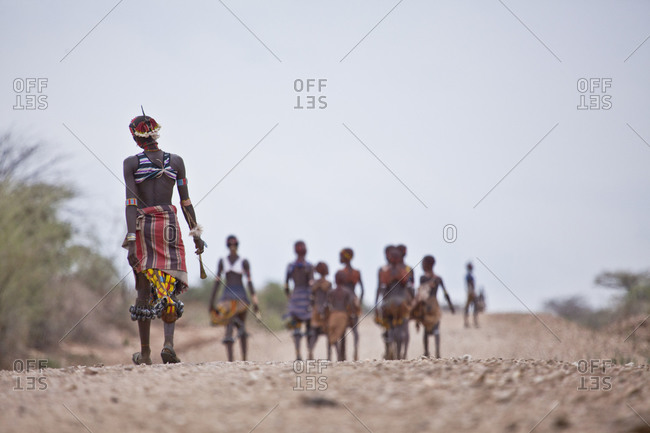 Africa - July 28, 2011: Hamar tribes people walking along a gravel road