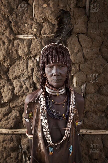 Africa - July 29, 2011: Portrait of an Hamar woman against a mud wall
