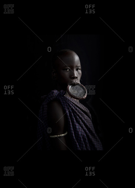 Africa - July 31, 2011: Portrait of a Mursi woman on a dark background