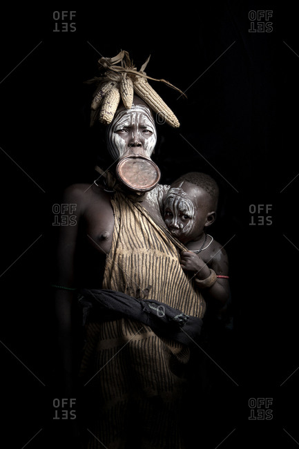 Africa - July 31, 2011: Portrait of a Mursi woman and her child on a dark background