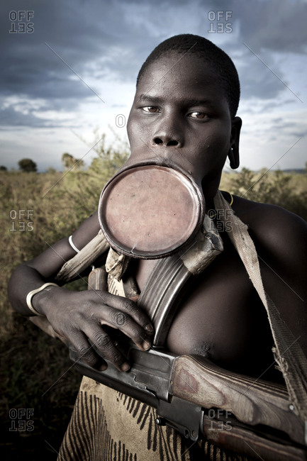 Africa - August 1, 2011: Portrait of a Mursi woman with a lip plate carrying a gun