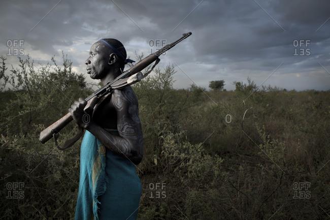 Africa - August 1, 2011: Portrait of a Mursi tribesman carrying a gun