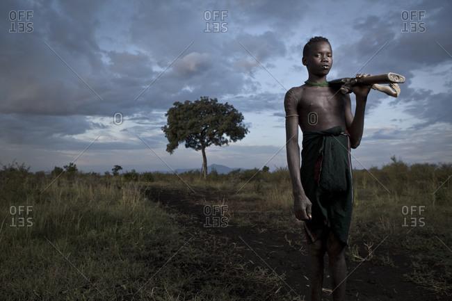 Africa - August 1, 2011: Portrait of a Mursi boy carrying a gun