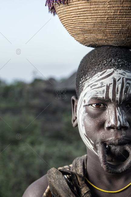 Africa - August 1, 2011: Portrait of a Mursi girl with a lip plate balancing a basket on her head