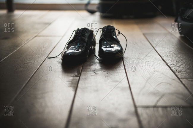 Grooms shoes waiting on parquet floor on wedding day.