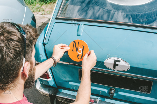 Graphic designer arranging the sticker on the vintage care with the initials of the bride and groom