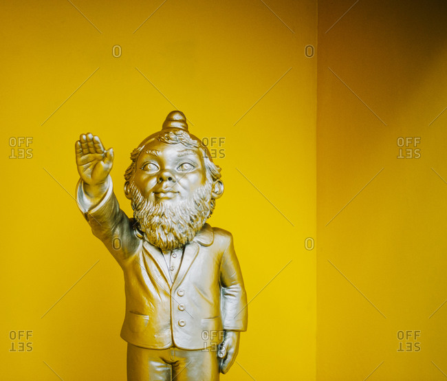 Garden gnome with raised hand on yellow background