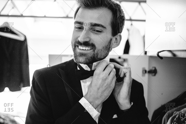 Smiling elegant groom arranging his bow tie