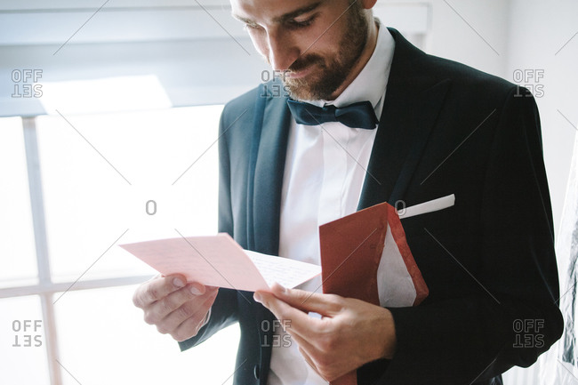 Groom with content face reading emotional letter from his bride before arriving at the weeding to meet her
