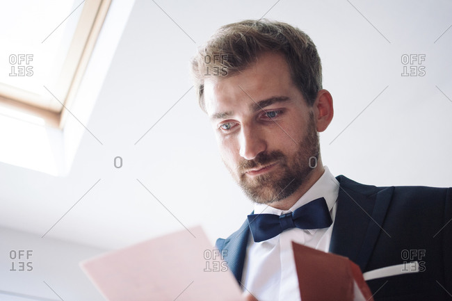 Groom with tears in the eyes reading emotional letter from his bride before arriving at the weeding to meet her