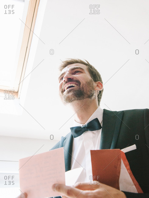 Groom smiling  after reading emotional letter from his bride before arriving at the weeding to meet her