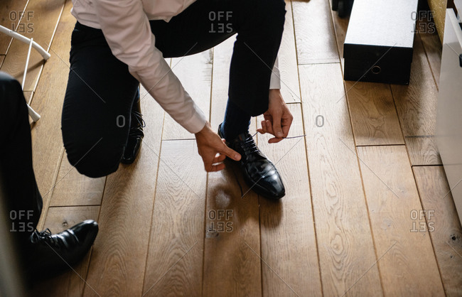 Groom tying his shoes before wedding