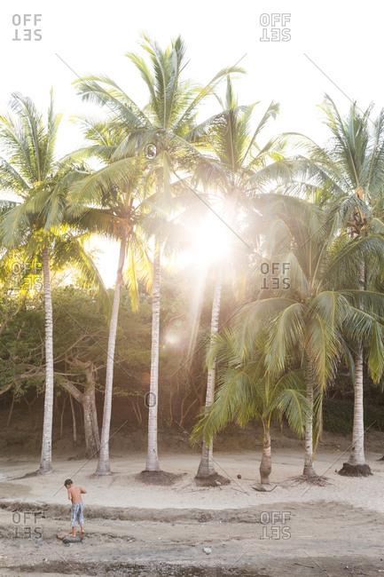 Boy on sunlit beach, Mexico