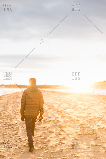 A man on beach during sunset stroll